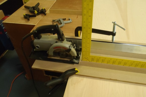 Cutting Guide for Handheld Trim Saw.  Metal ruler is used as spacer between a scrap MDF strip that providers support for the saw and minimizes chipping of the veneer.
